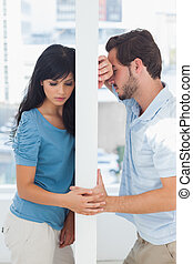 Couple are separated by white wall having relationship...