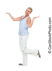 Happy woman standing with hands up and leg raised on white...