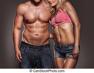 Fitness image of a man and woman's torso isolated on black