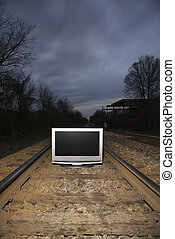 Television on train tracks - Flat panel television set on...