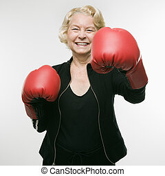 Woman punching. - Caucasian senior woman wearing boxing...