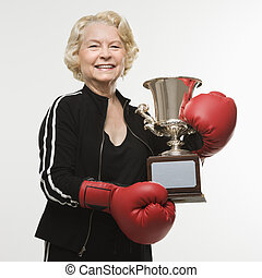Woman with trophy. - Caucasian senior woman wearing boxing...
