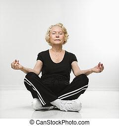 Senior woman meditating. - Caucasian senior woman sitting in...
