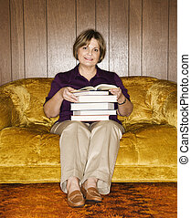Woman holding books - Caucasian middle aged woman sitting on...