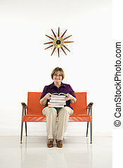 Woman holding books. - Caucasian middle aged woman sitting...