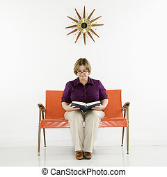 Woman reading book - Caucasian middle aged woman sitting...
