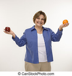 Woman holding fruit. - Caucasian middle aged woman holding...