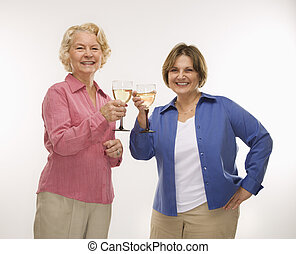 Two women toasting wine - Caucasian senior woman and middle...