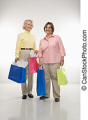Women holding bags. - Caucasian senior woman and middle aged...
