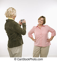 Women using digital camera. - Caucasian senior woman taking...
