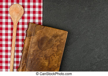 Wooden spoon and coockbook on a slate plate