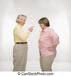 Women arguing - Caucasian senior woman and middle aged woman...