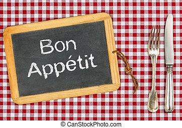 Blackboard with the text Bon Appetit on a checkered...
