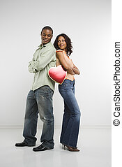 Couple holding valentine heart - Studio shot of multi-ethnic...