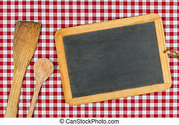Empty blackboard with wooden spoons on a red checkered table cloth