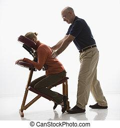 Man massaging woman - Caucasian middle-aged male massage...