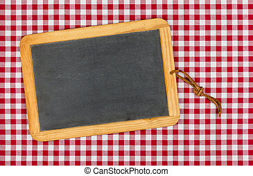 Empty blackboard with chalk on a red checkered table cloth