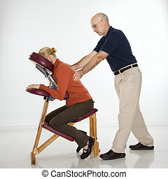 Man massaging woman. - Caucasian middle-aged male massage...