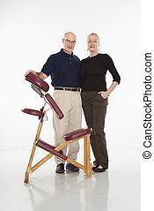 Massage therapists. - Caucasian middle-aged male massage...