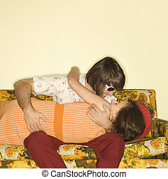 Couple kissing on sofa.