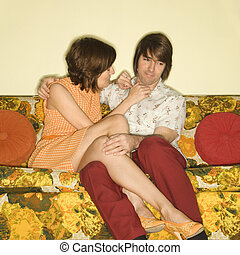 Couple on sofa. - Pretty Caucasian mid-adult woman flirting...