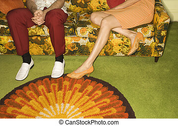 Couple on sofa. - Female legs playing footsie with male legs...