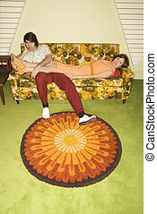 Couple on sofa - Caucasian mid-adult woman lying on colorful...
