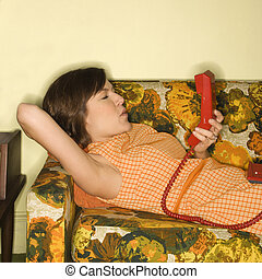 Woman on telephone - Pretty Caucasian mid-adult woman lying...