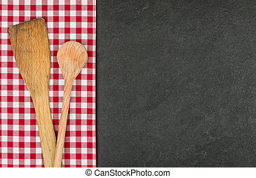 Wooden spoon on a slate plate with a red checkered...