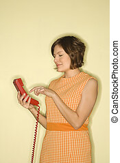 Woman dialing telephone - Pretty Caucasian mid-adult woman...