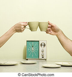 Hands toasting cups - Caucasian male and female hands...