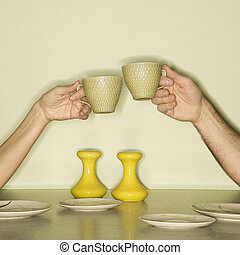 Hands toasting cups.