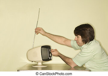 Man tuning in television. - Side view of Caucasian mid-adult...
