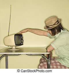 Man tapping retro TV - Side view of Caucasian mid-adult man...