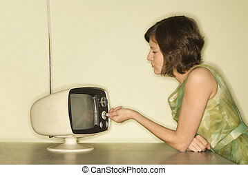 Woman dialing television. - Side view of pretty Caucasian...
