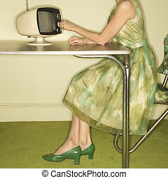 Woman dialing television - Side view of Caucasian mid-adult...