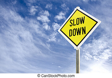 Slow Down yellow road sign on blue sky with clouds...