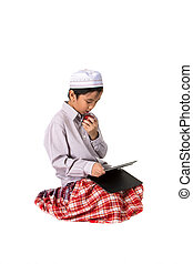 Muslim boy eating apple and play tablet.