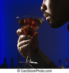 Man drinking martini - Close up profile of African American...