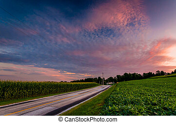 Sunset clouds over a country road and farm fields in Southern York County, Pennsylvania.