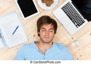 too much work - young man sleeping on the floor with laptop