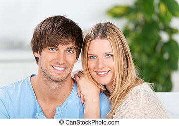 young smiling couple in love on the sofa
