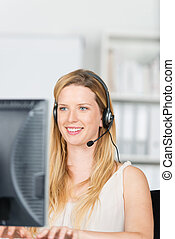 woman working with headset and computer
