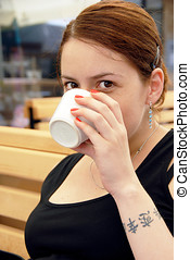 Young woman portrait drinking coffee - young caucasian...