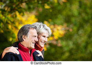 Laughing affectionate senior couple standing close together...