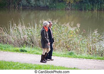 Senior couple walking alongside a lake