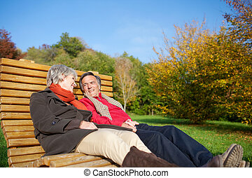 Senior couple relaxing in the autumn sun reclining side by...