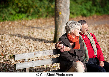 Senior couple in park - Smiling senior couple sitting on the...
