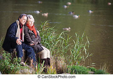 Loving mature couple sitting and looking on the river side