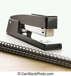 Stapler on notebook - Black stapler on top of a spiral bound...